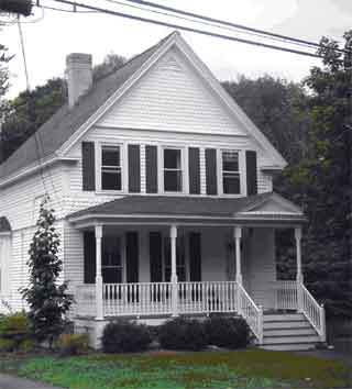 The porch of this front-gabled house has a pediment over the entrance stairs.