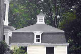 The mansard roof of this carriage house is topped by a cupola