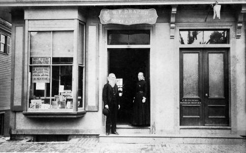 Warren F. Draper at his Book & Stationary store.  The woman is probably Mary Ann (Stanley) Richards who was Draper's clerk for 35 years. Dentist Charles H. Gilbert has his office on the second floor. Note the tooth sign over the entrance door