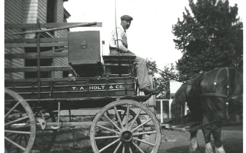 T. A. Holt wagon at the carriage house. Driver appears to be J. Warren Berry