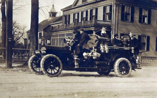Circa 1918 Fire truck zips past the Swift house on Main St.