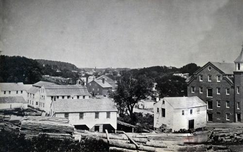 Circa 1875 - earlier mill buildings on both sides of the river next to the dam